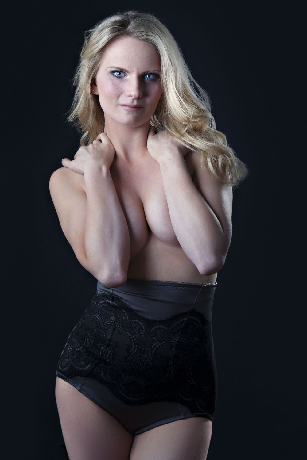 Sensual photo of a gorgeous blonde with hands in her neck showing cleavage for a boudoir photography session in Boston MA