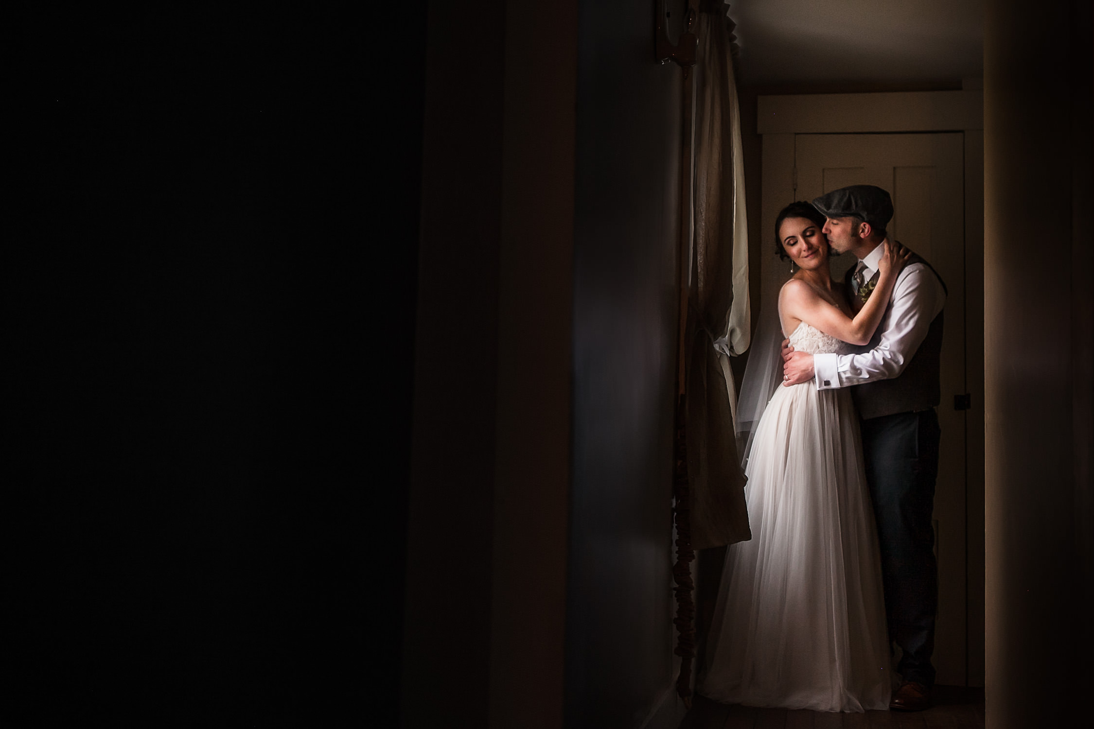 indoor portraits of bride and groom, couple kissing near the window at Harrington Farm wedding