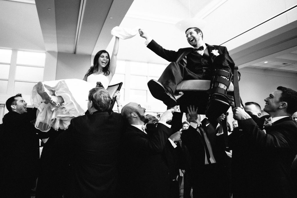 Massachusetts wedding photographer, bride and groom on a hoard chair jewish dance