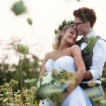 Couple in the fields taken romantic photos at a Harrington farm wedding