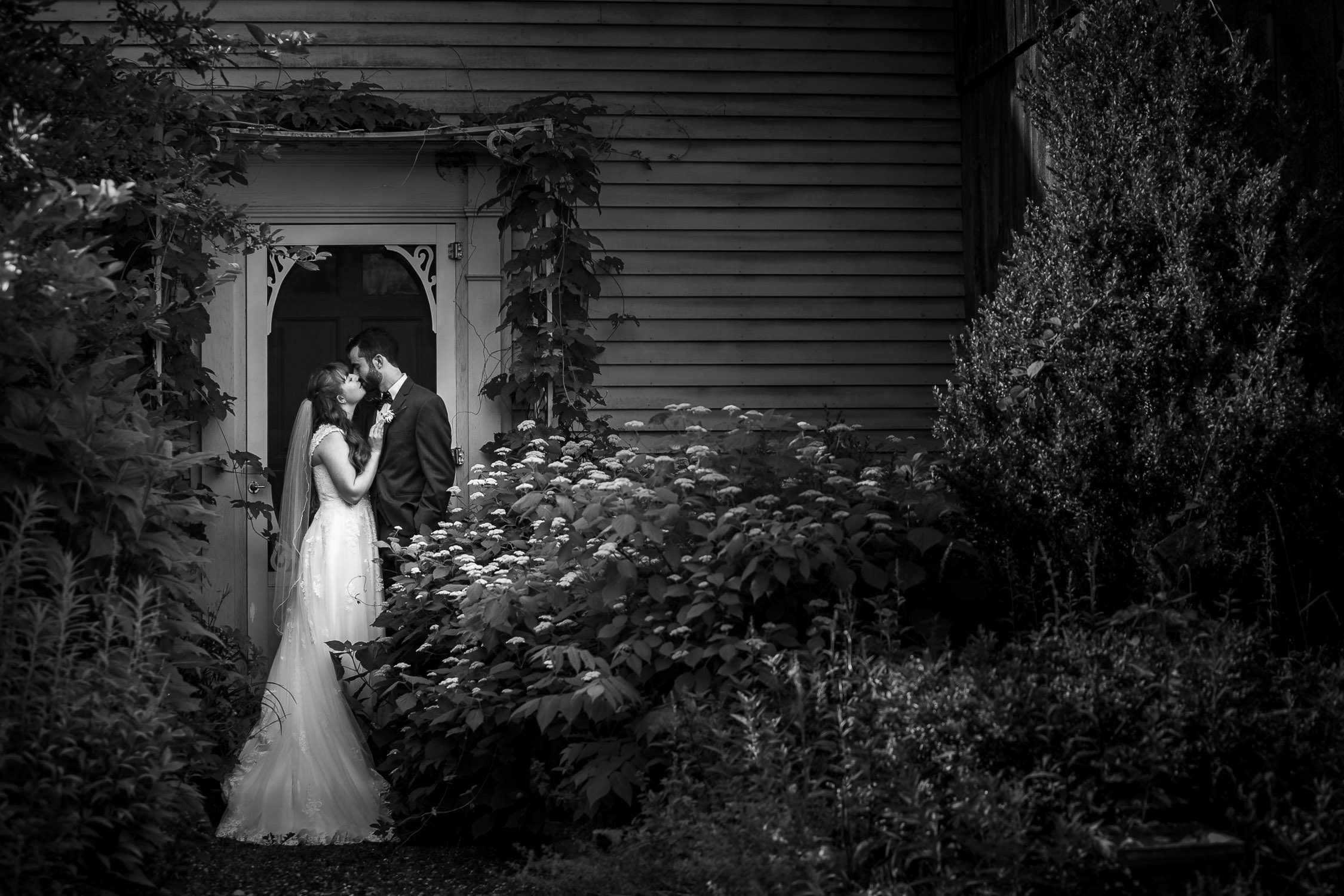 artistic BW photo of bride and groom near the barn for romantic photos at hartmans herb farm weddings