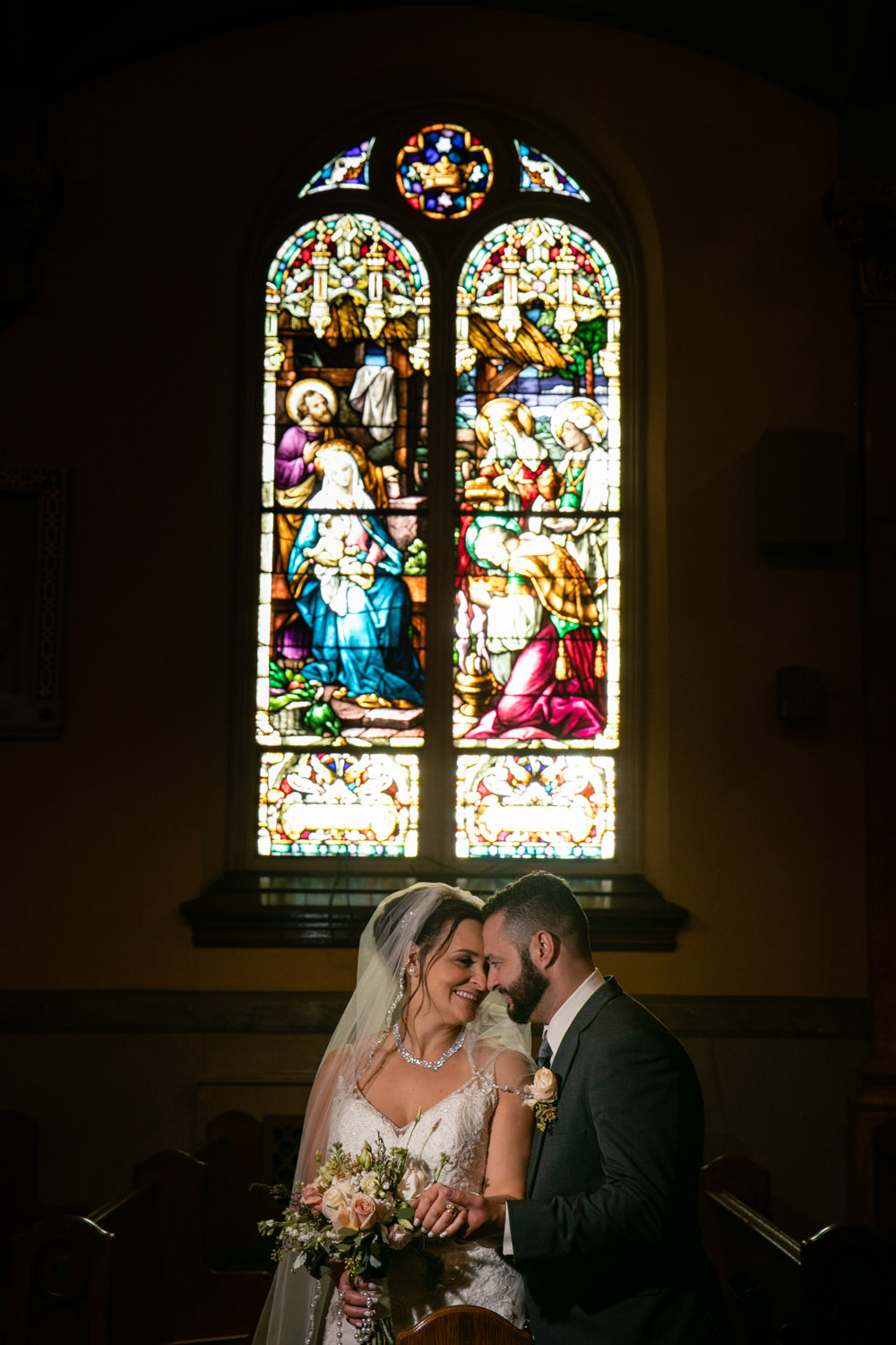 bride and groom in front of the stained glass Wedding at Holy Family Parish at St. Joseph's Church